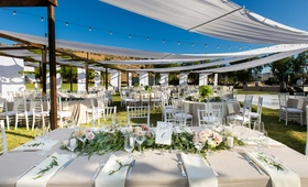 semi tented outdoor reception space with champagne colored tablescapes hanging lights low florals