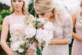Bride in Oleg Cassini wedding dress smells fresh bouquet