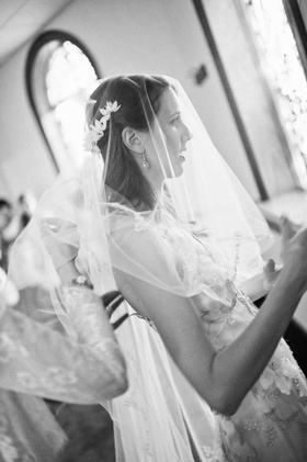 Black and white photo of bride with veil getting ready