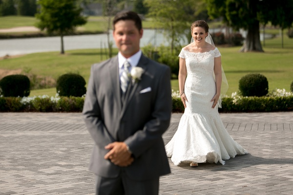 Bride in an off-the-shoulder, fit-and-flare Sottero and Midgley lace dress walks to groom in grey