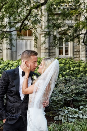 Bride in jeweled wedding dress from bella bianca couture veil blonde hair kissing groom in tuxedo
