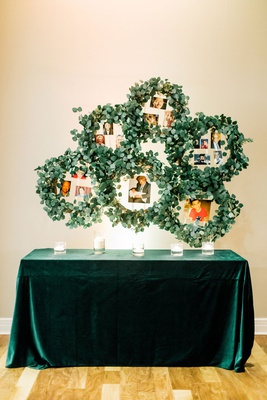 wedding reception emerald green velvet linen eucalyptus wreaths with family photos late loved ones