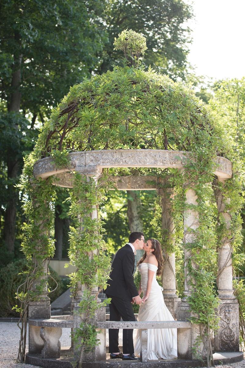 Bride in off shoulder Pnina Tornai wedding dress kissing groom in tuxedo at Oheka Castle under dome