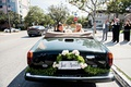 Bride and groom in convertible rolls royce corniche car from ceremony to reception