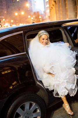 bride in monique lhuillier ball gown exits limo while holding skirt