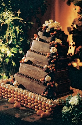 Five layer wedding cake with white flowers, berries, and oranges