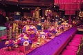 indian wedding sangeet, bright colors, floating candles in blue water, purple and fuchsia tablescape