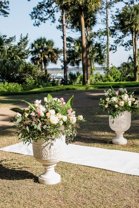wedding ceremony outdoor urn with greenery white pink flowers trees overlooking water grass