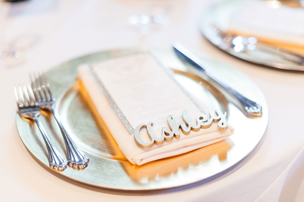 Place setting with charger plate gold paint wood place cards laser cut names on top of menu card