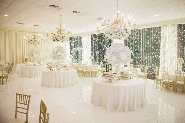 Ballroom white and gold wedding reception decor white flower arrangements gold chairs chandeliers