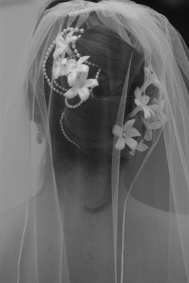Black and white picture of wedding hairstyle with pearls, flowers, and veil