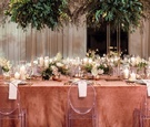 head table at wedding with ghost chairs and tall arrangements of greenery