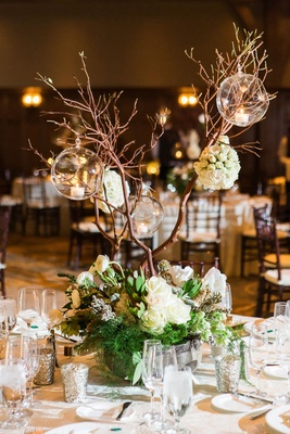 Wedding reception greenery white flowers tall branches with glass orb candholders centerpiece rustic