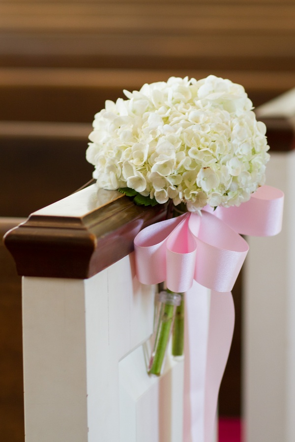 White hydrangeas tied to church pew with pink ribbon