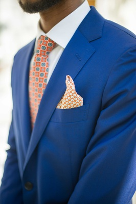 a groom wearing a bright blue tuxedo accented by a tie and pocket square an orange blue pattern