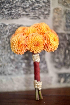 Bridesmaid's bouquet of orange dahlias wrapped in burgundy fabric