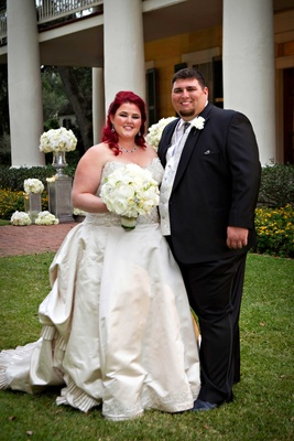 Bride in strapless Eve of Milady ball gown with bright red hair and groom in tuxedo with silver vest