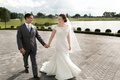 Bride in an off-the-shoulder, fit-and-flare Sottero and Midgley lace dress, groom in grey suit, pond