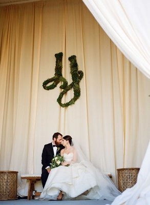 Bride and groom at rustic wedding greenery sculpture in monogram wall art on drapery