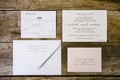 a white and pink invitation suite with silver and gold calligraphy