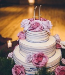 Wedding cake three layer with purple edge ruffles and gold monogram cake topper fresh flowers pink