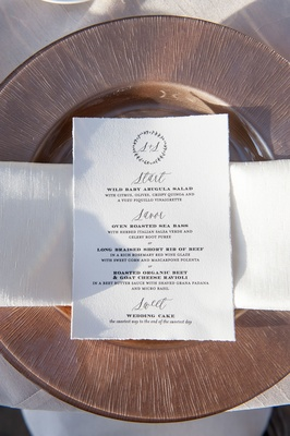 Wedding menu with torn edges, monogram at top, calligraphy and menu selections