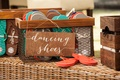 Wedding reception flip flops in crate with dancing shoes calligraphy wooden sign at outdoor receptio