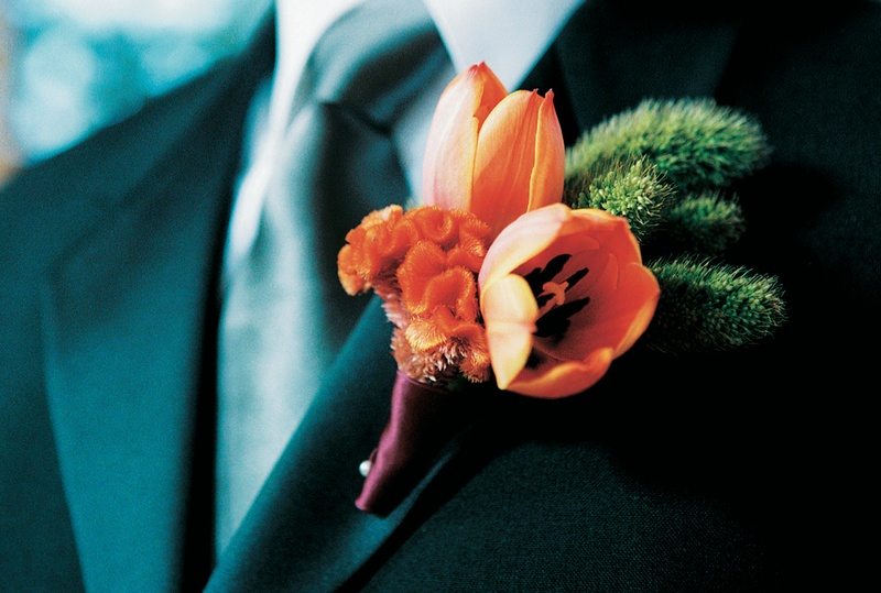 boutonniere of orange tulips with green succulents