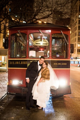 Bride in fur stole white wedding dress on back of trolley with groom in tuxedo bow tie chicago