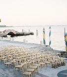 Villa inspired wedding in Miami wood chairs set up on walkway by water Vizcaya in Miami
