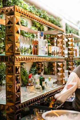 Wedding cocktail hour reception bar shelves rose gold pyramid studs with liquor and glassware