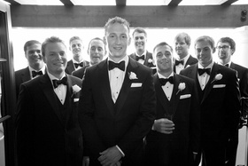 Black and white photo of groom and groomsmen in tuxedos and bow ties