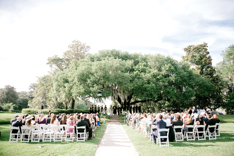 wedding reception under large tree up on steps stone white flower petal aisle white chairs guests
