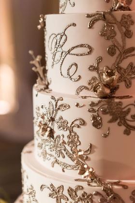 Wedding cake with blush fondant and gold frosting embellishments monogram and flowers