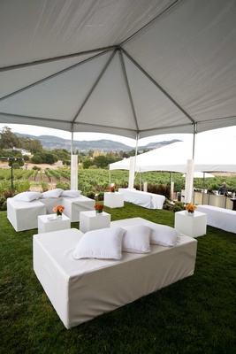 white couches and tables under white tent next to vineyard