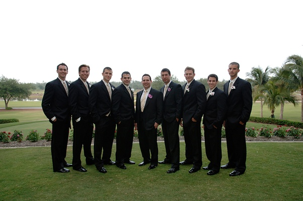 Groom and best man with groomsmen on grass lawn