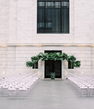 wedding ceremony cleveland museum of art oval clear guest chairs and tropical greenery chuppah