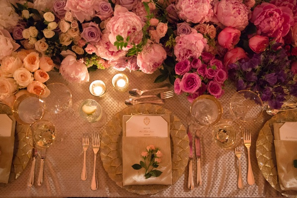 Wedding reception place setting with rosebuds and pink white purple flowers at long table