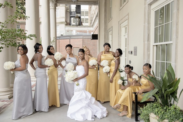 Bride in mermaid gown with nine gold and silver bridesmaid dresses