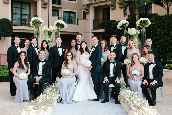 Bride and groom with bridesmaids in light blue silver dresses and groomsmen in tuxedos bow ties