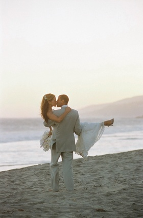Groom picks up bride on beach and walks towards ocean