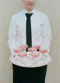 Server holding silver tray of coupe champagne glasses with pink drink