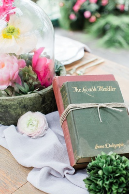 two vintage books tied with twine as centerpiece on wedding reception table
