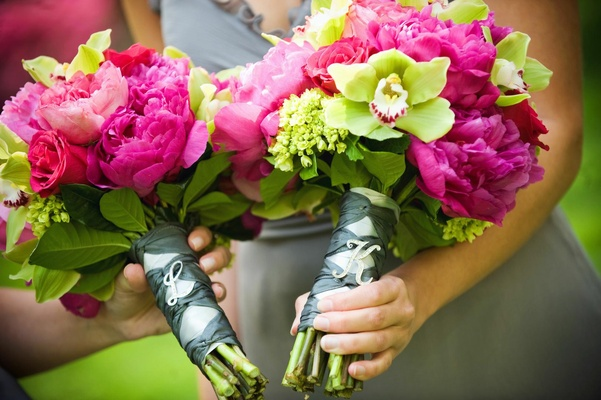 Bridesmaids' bouquets of pink and green flowers with personalized pins