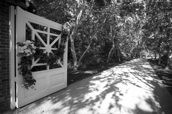 Black and white photo of long driveway and gate