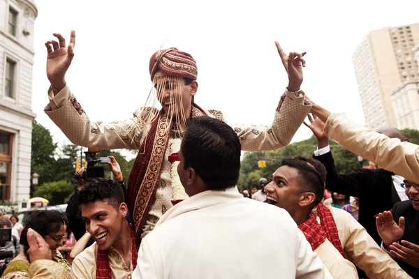 Groomsmen pick up Indian groom in traditional attire