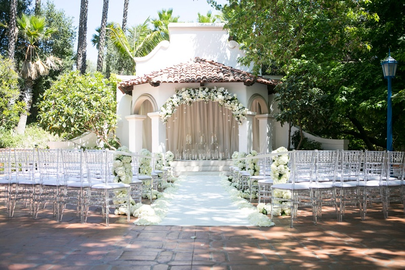 Clear Guest Chairs And Ivory Floral Arch