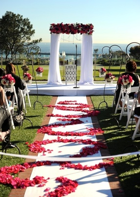 White aisle with patterned petals and wedding canopy