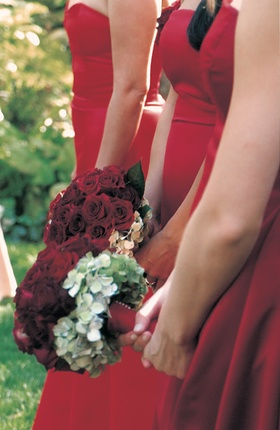 Bridesmaids in sleek red dresses with red bouquets