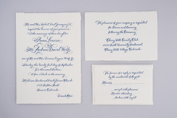 Wedding invitations with blue calligraphy on white paper